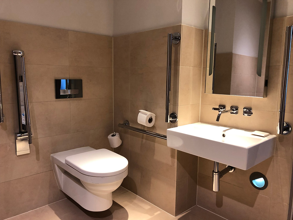 Hotel bathroom - toilet and sink with mirror and chrome grab bars