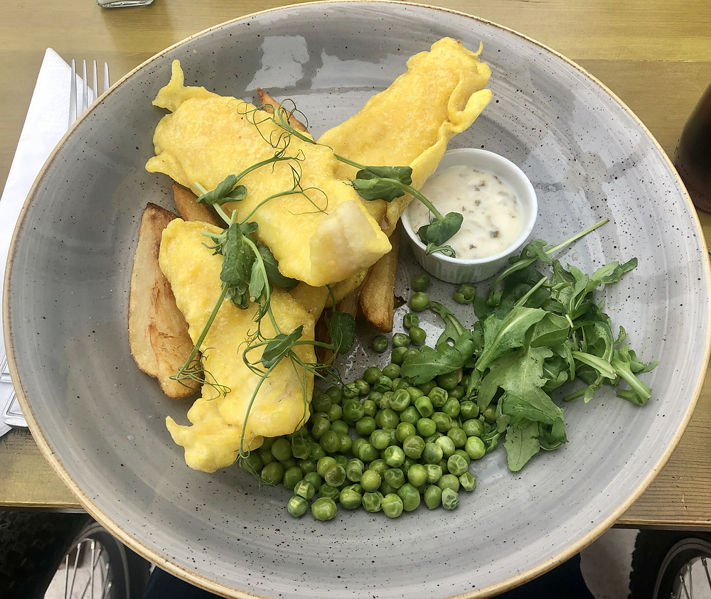 A plate of fish, chips and peas