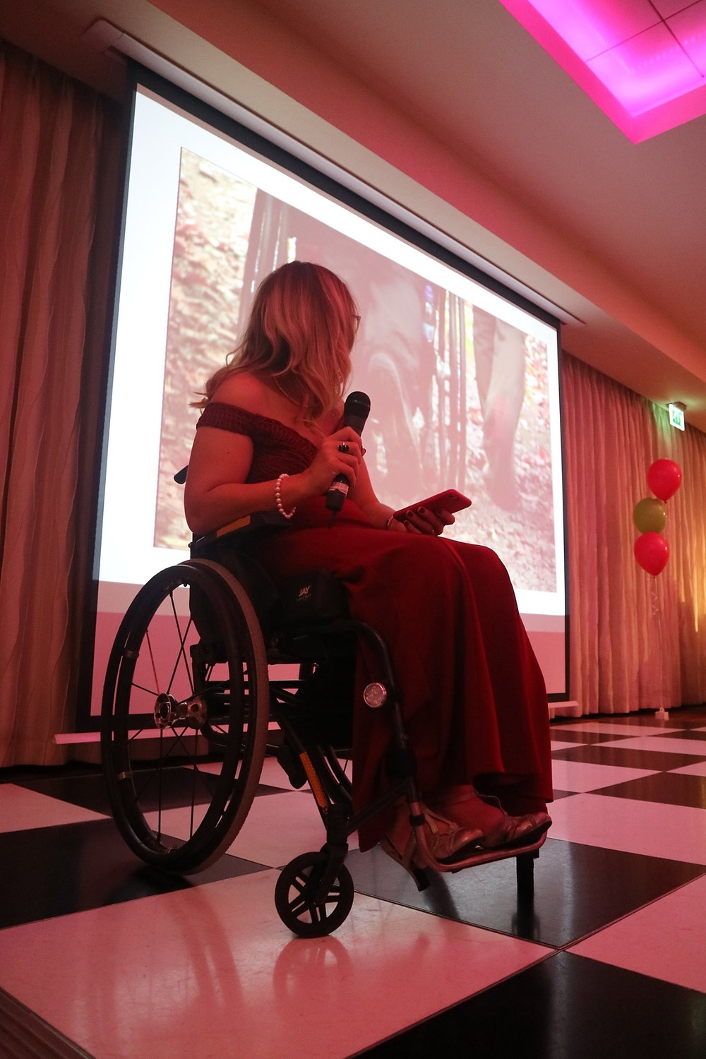 Carrie-Ann on stage in her wheelchair holding a microphone