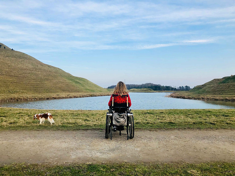 Photo of Carrie-Ann in her wheelchair taken from behind, overlooking a lake in Northumberland. Her dog Poppy looks at the camera.