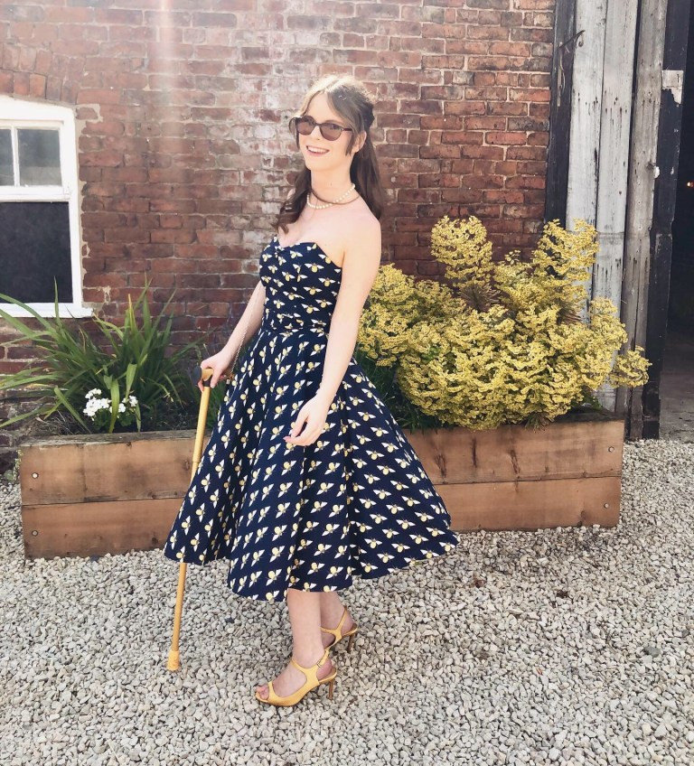 Chloe standing in a garden, wearing sunglasses, a 50s style dress, yellow heels and using a yellow stick