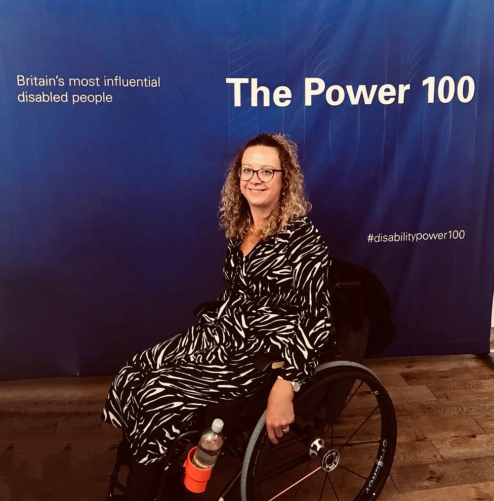 Carrie-Ann sits in front of a purple banner with the Power 100 branding