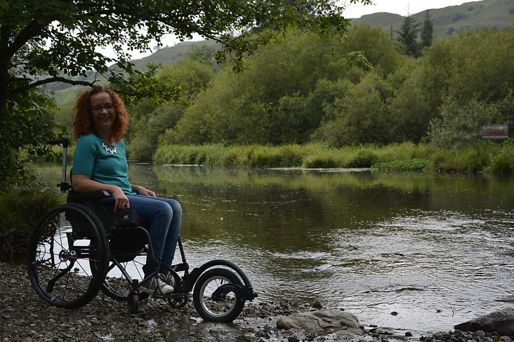 Carrie-Ann in her wheelchair in front of a lake