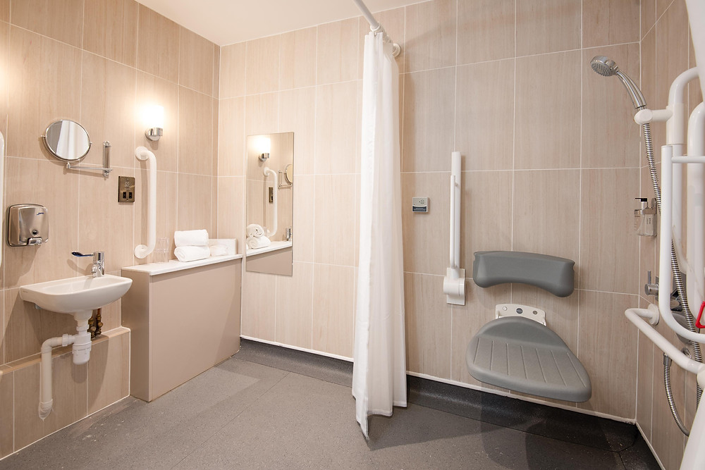 Tied hotel bathroom with wet room shower, fold down seat, grab bars, sink and mirror