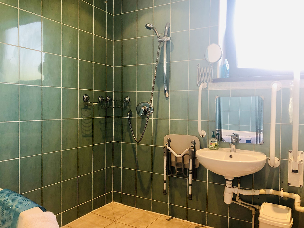 Quarters Lancaster bathroom - turqoise tiles, wet room shower and lowered sink with grab bars