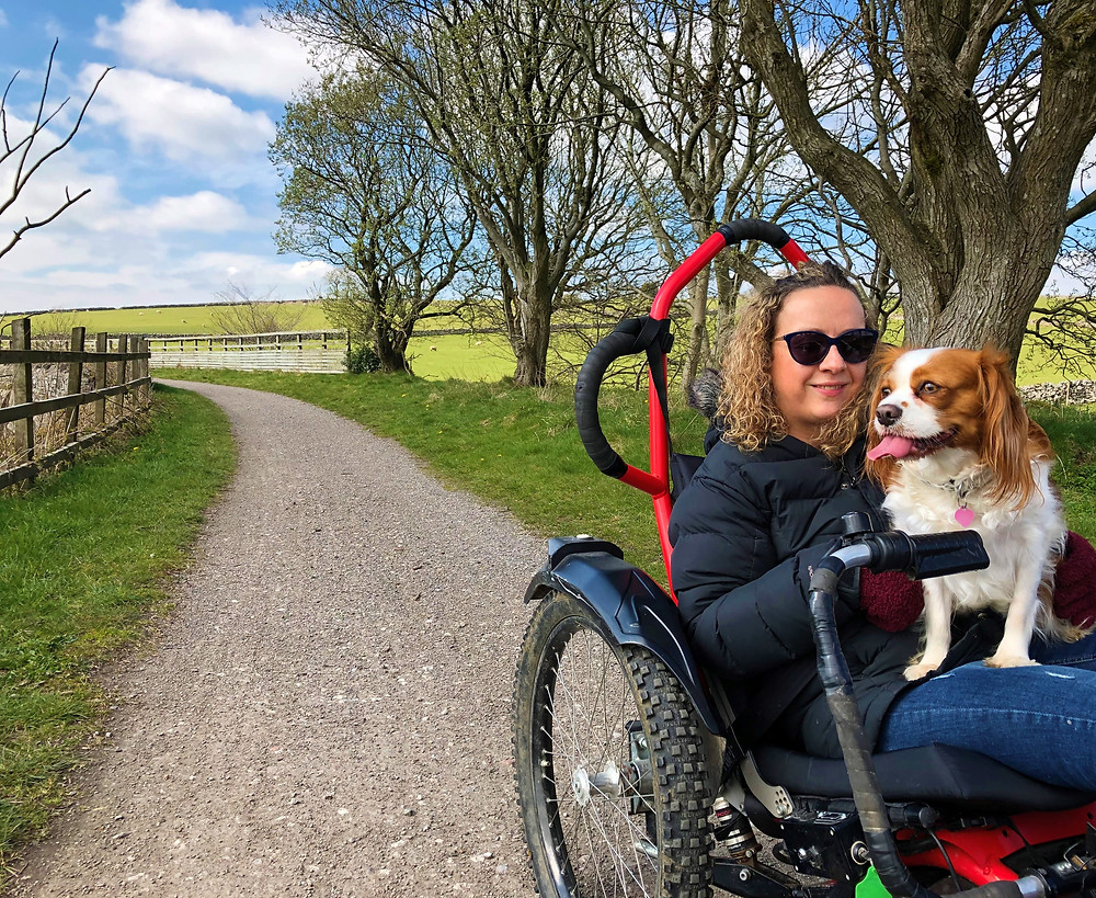 Carrie-Ann on an off-road wheelchair with her dog on her knee
