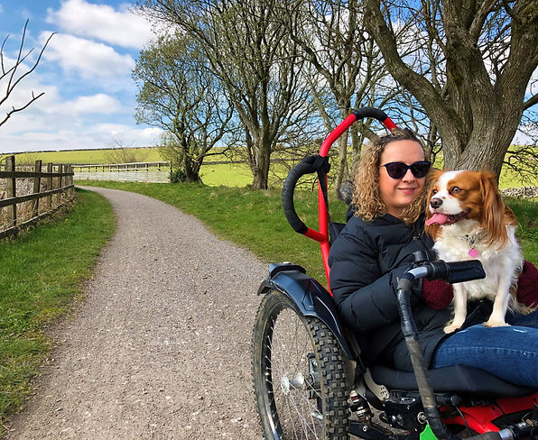Carrie-Ann on an off-road wheelchair with her dog sat on her lap