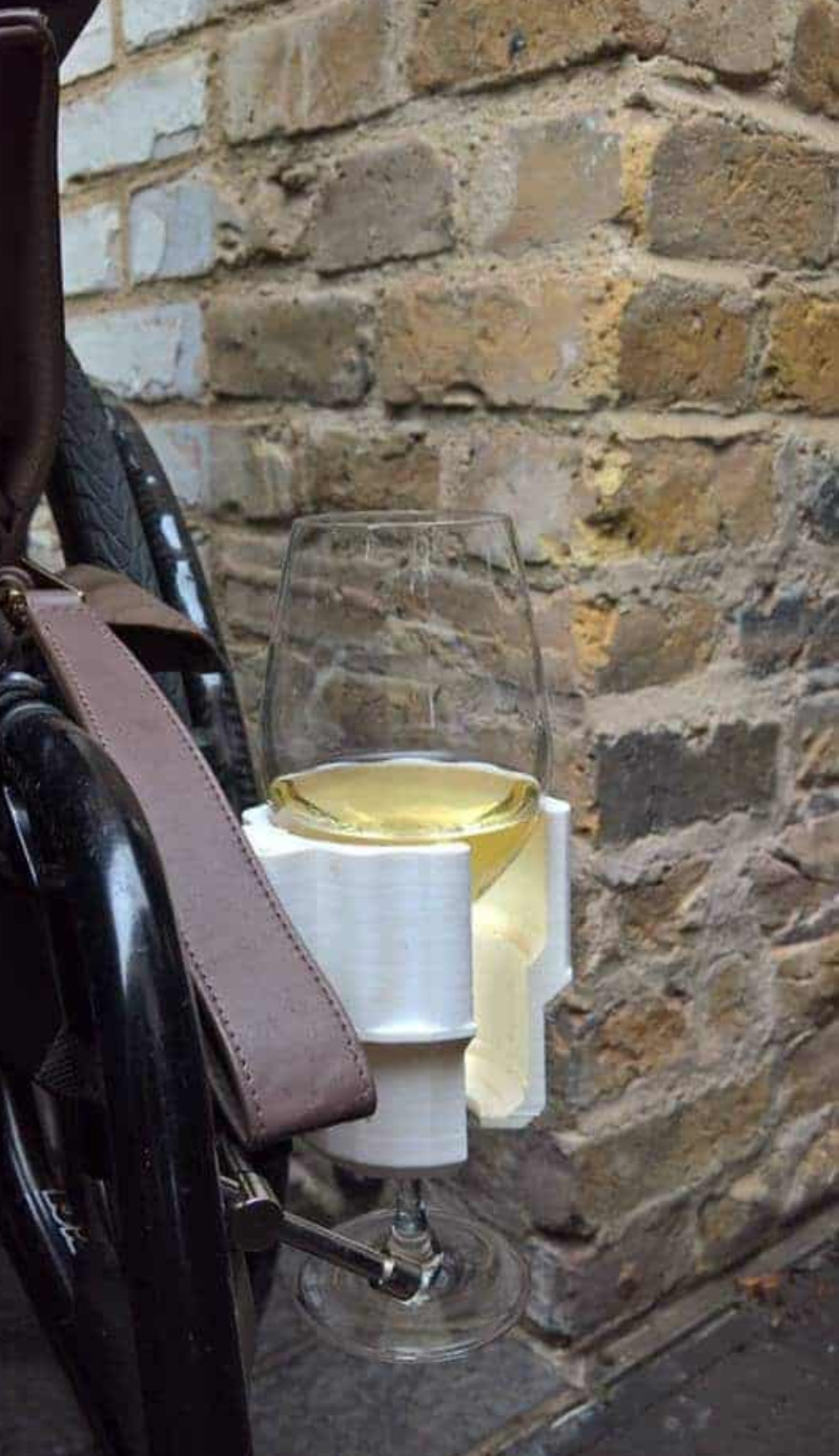 White DRINK universal glass holder attached to wheelchair, holding wine glass