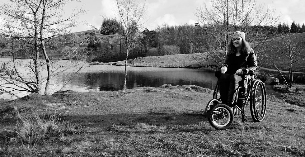 Black and white photo of Carrie-Ann in her wheelchair in the Lake Disctict countryside