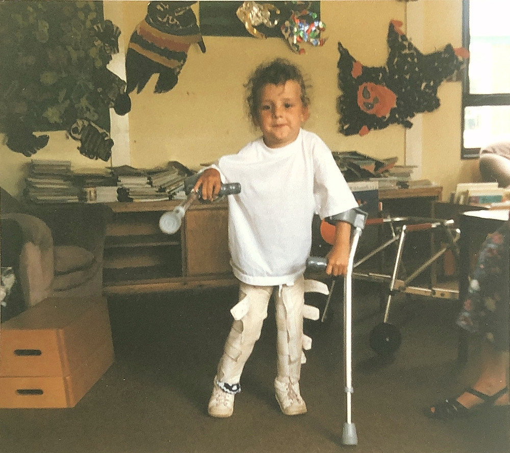 Young Carrie-Ann at school using crutches and calipers
