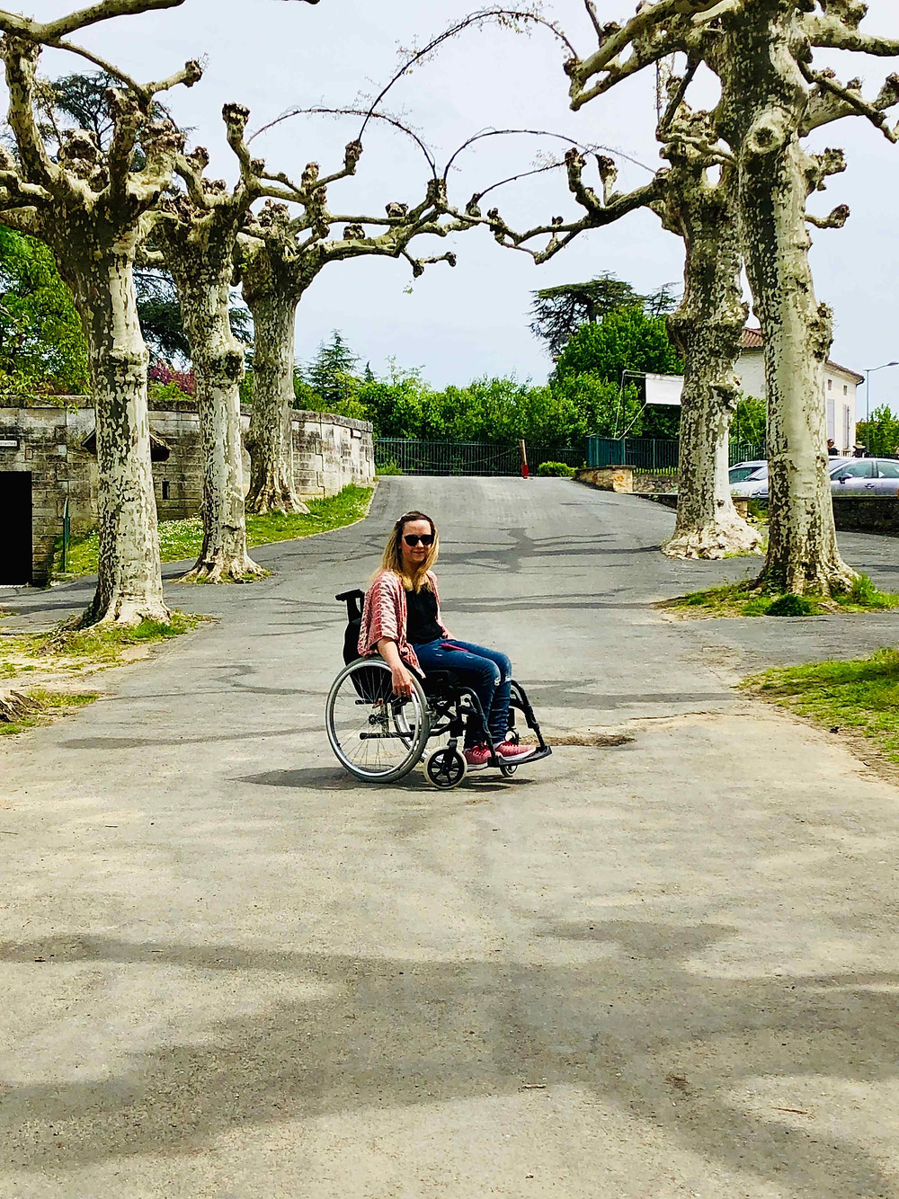 Carrie-Ann Lightley Disabled Travel Blogger under the trees in Brantome