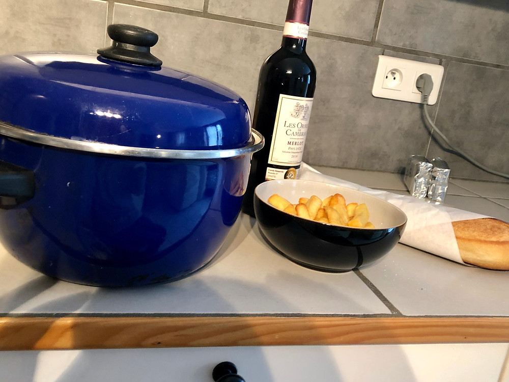 Welcome pack - pot containing cooked pasta, bottle of red wine, bowl of chips and loaf of fresh bread
