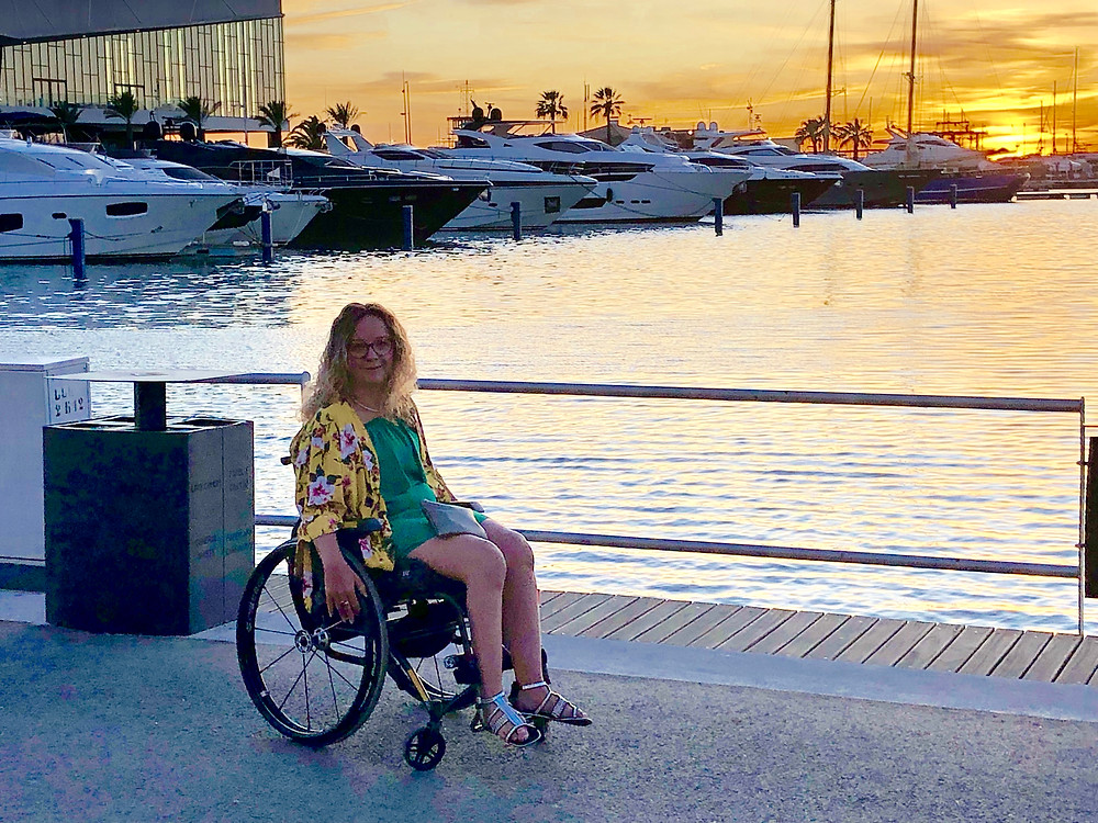 Carrie-Ann is sitting in her wheelchair in front of a marina in Vilamoura, Portugal. The sun is setting behind her.