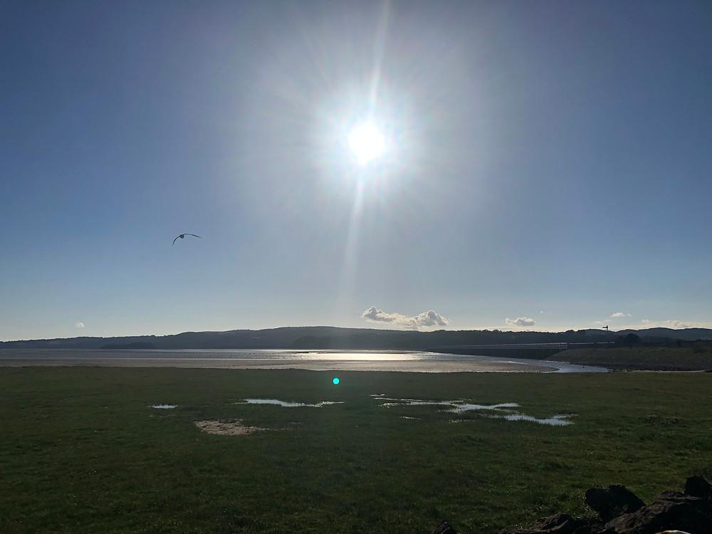 The sun shining over Arnside beach