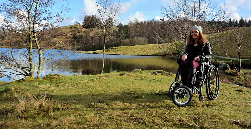 Carrie-Ann Lightley Disabled Travel Blogger sitting in her wheelchair next to a lake on the green grass