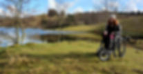 Carrie-Ann sits in her wheelchair in front of a tarn in the Lake District.