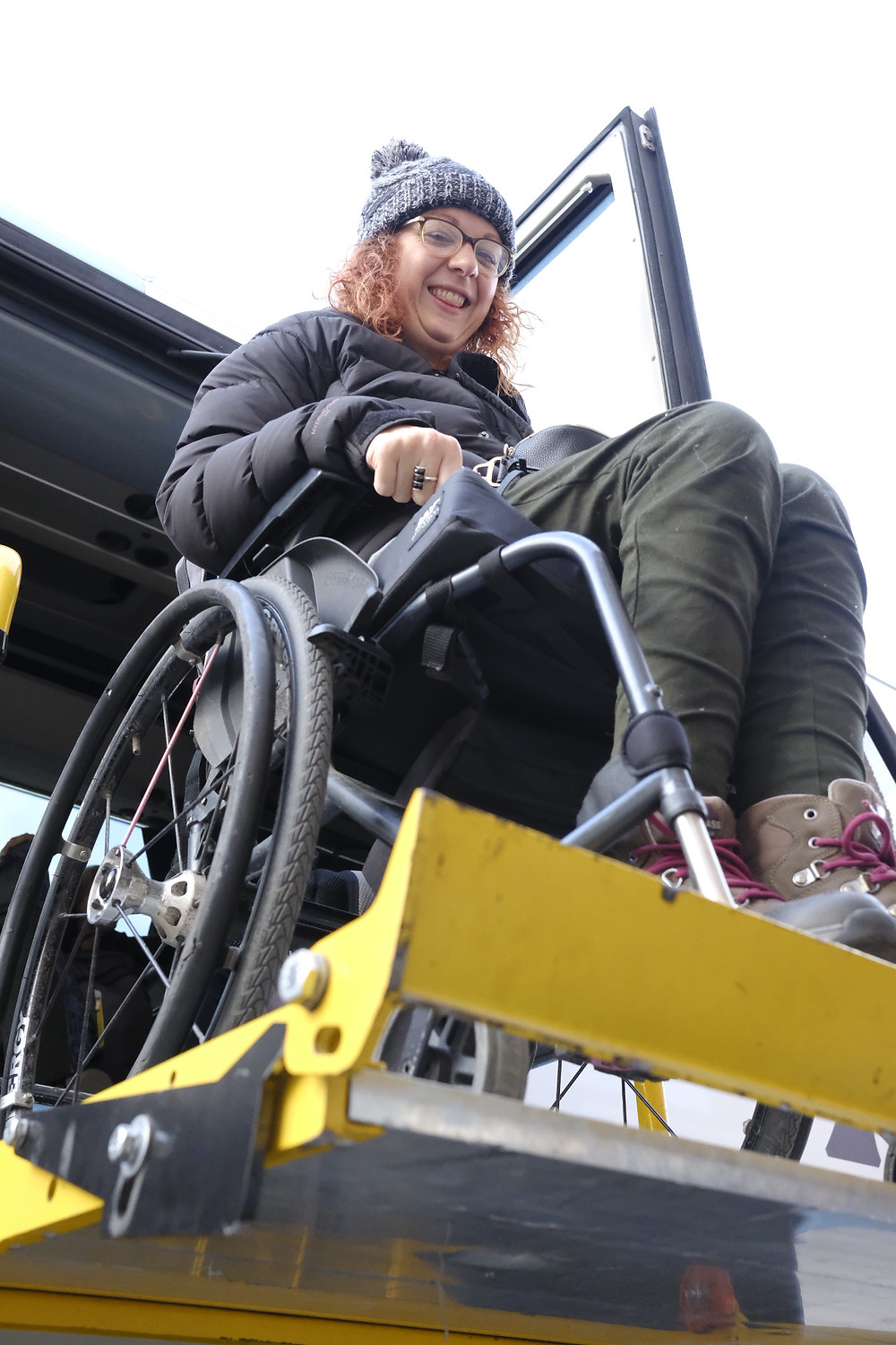 Photo shows a woman sitting in a wheelchair, using a platform lift to exit a coach.