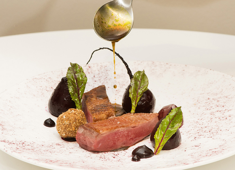 Duck fillet with sauce being poured over