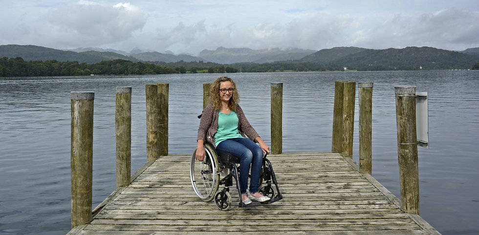 Carrie-Ann sitting in her wheelchair on a jetty