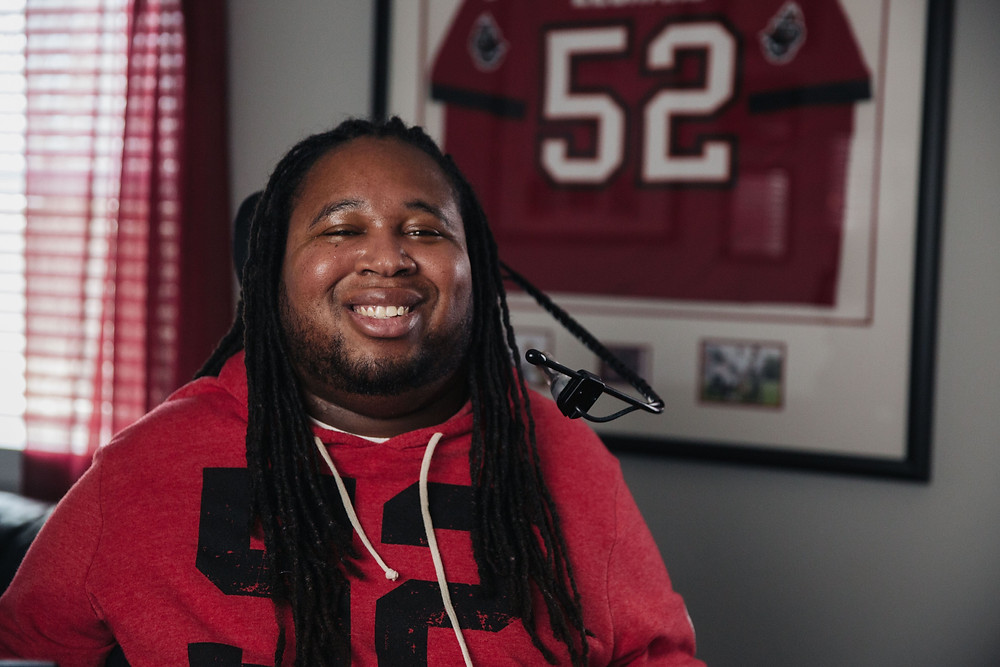Eric LeGrand sitting in his wheelchair in front of a framed football jersey