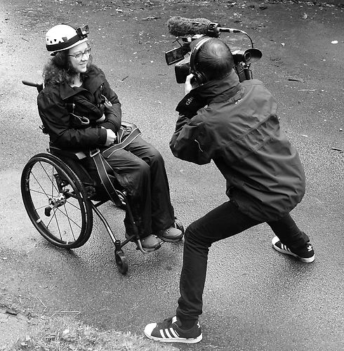 Carrie-Ann wearing waterproofs, a hard hat and a go pro. A camera man stands in front of her filming.