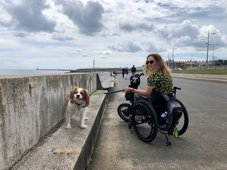 Carrie-Ann sitting in her wheelchair with her powered bike on the front. She's looking over her shoulder and smiling. Her small dog sits next to her on a wall.