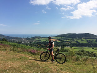 Mountain biker on Fire Beacon Hill with view down to Sidmouth
