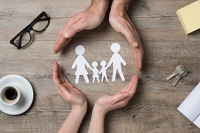 Close up of female and male hands protecting a paper chain family. Top view of two hands form a circ