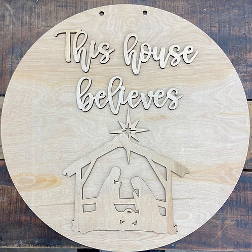 Wooden doorhanger with nativity and text that says this house believes