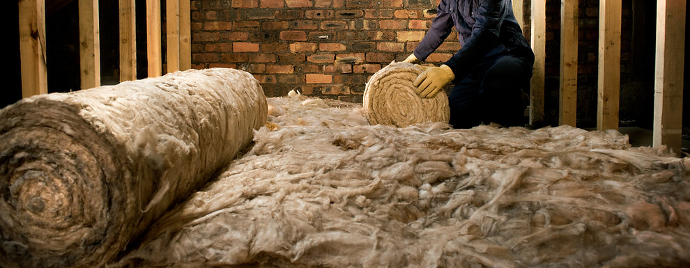 A worker laying loft insulation