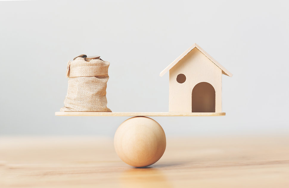 Wooden home and coins money in bag on wo