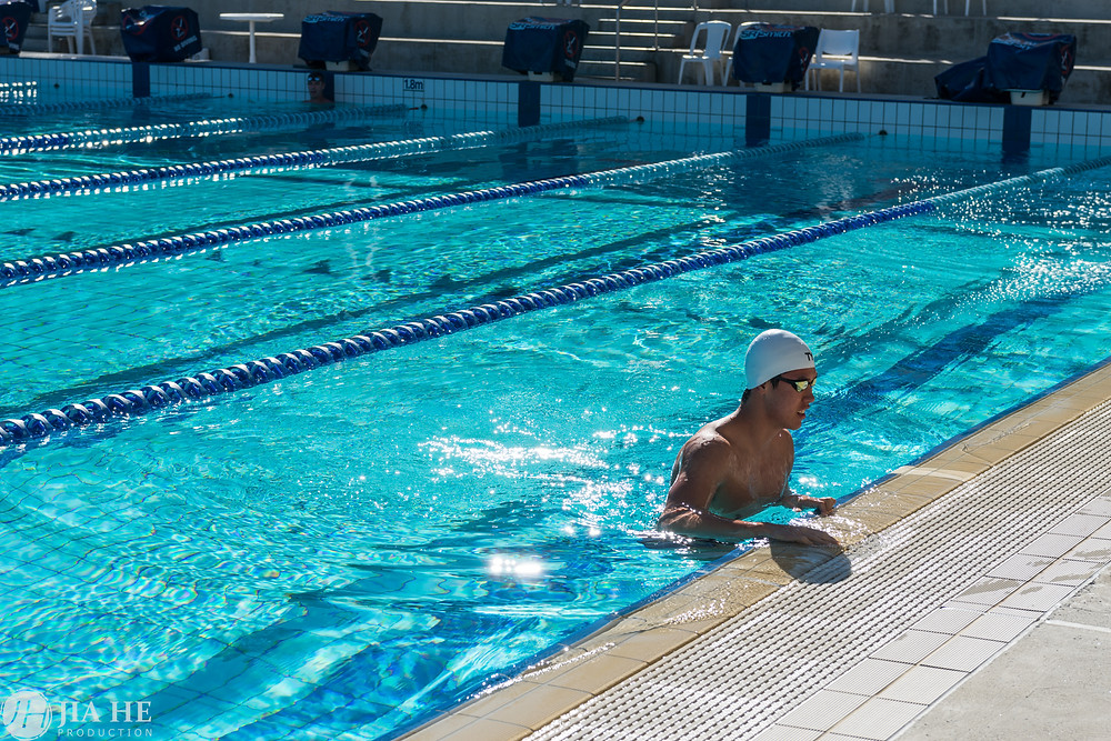 A swimmer is taking a rest in the swimming pool