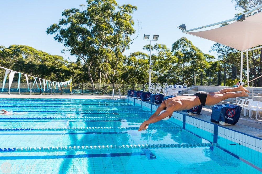 A swimmer is jumping into the swimming pool