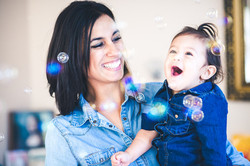 mom and daughter laughs at soap bubbles
