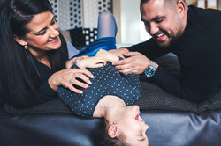 mother and father tickling their daughter