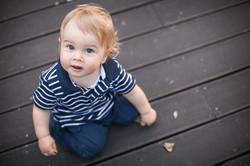 boy sitting on a wooden floor