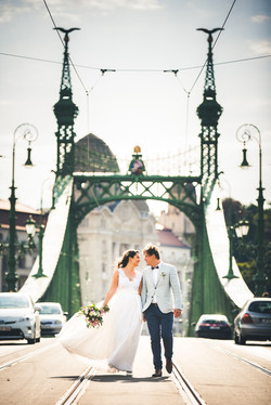 bride and groom walking on the liberty bridge budapest