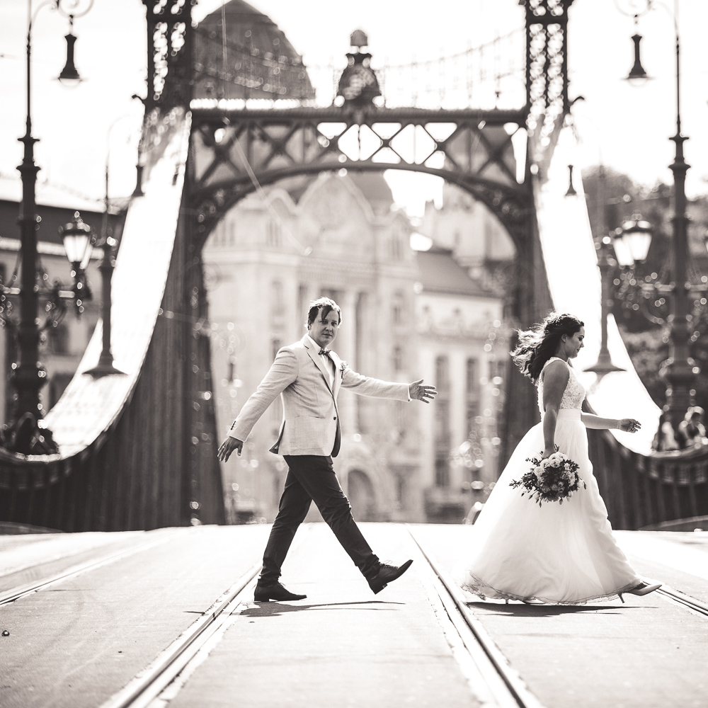 bride and groom walking on a bridge
