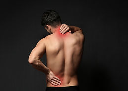 Young man suffering from back pain on bl