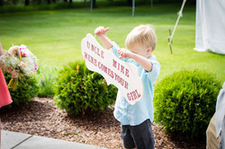 Little Man holding ceremony sign
