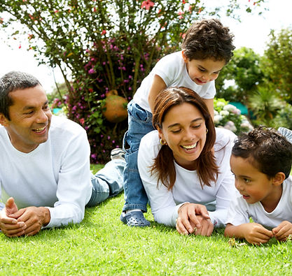 A family rolling around in the grass laughing