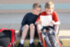 Two boys rading a paper sitting on a curb outside of chool
