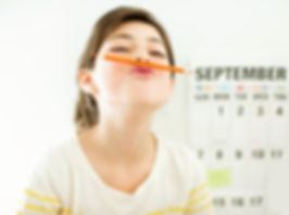 A girl balancing a pencil on her upper lip