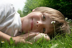 A boy smiling and laying down in the grass
