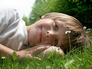 A boy smiling and laying in grass
