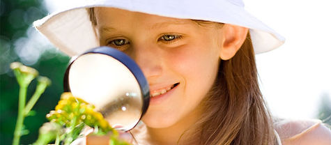 A girl with a hat looking through magnifying glass at a flower