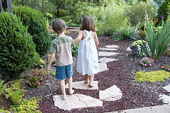 Children holding hands walking down a stone path