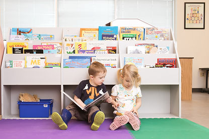 A boy and a girl sittng in a reading section of a classroom reading books