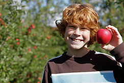 A boy holding an apple and smilng
