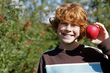 A bo with red hair smiling and holding a apple